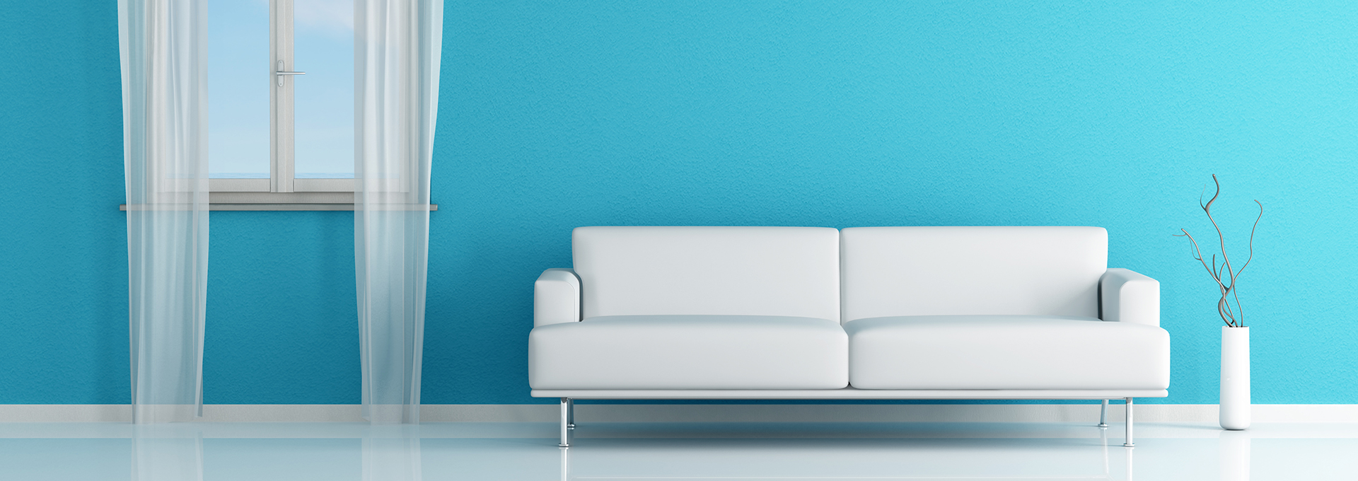 A white modern couch sits next to a teal blue wall with a white vase and white window - Design Accounting Solutions